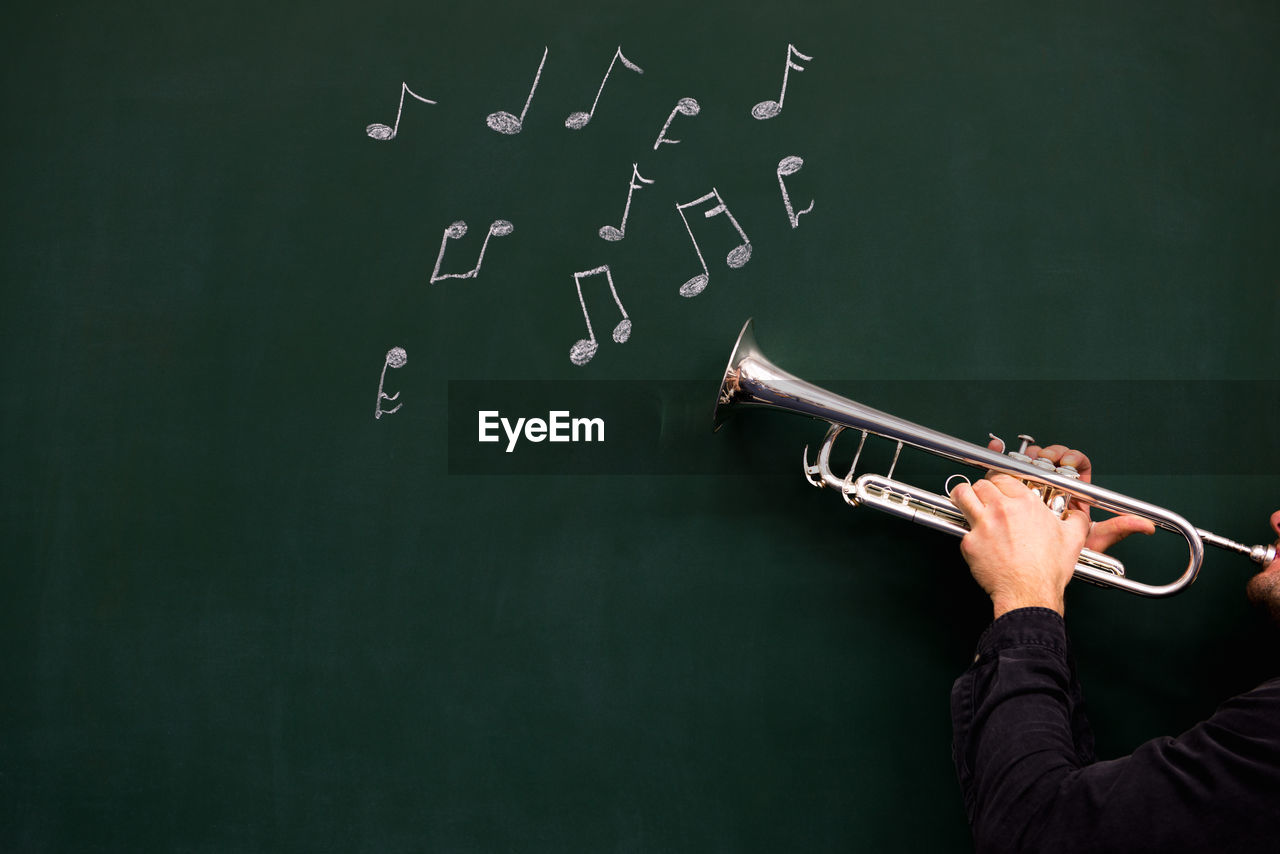 Cropped Hands Of Man Holding Trumpet By Musical Notes On Blackboard