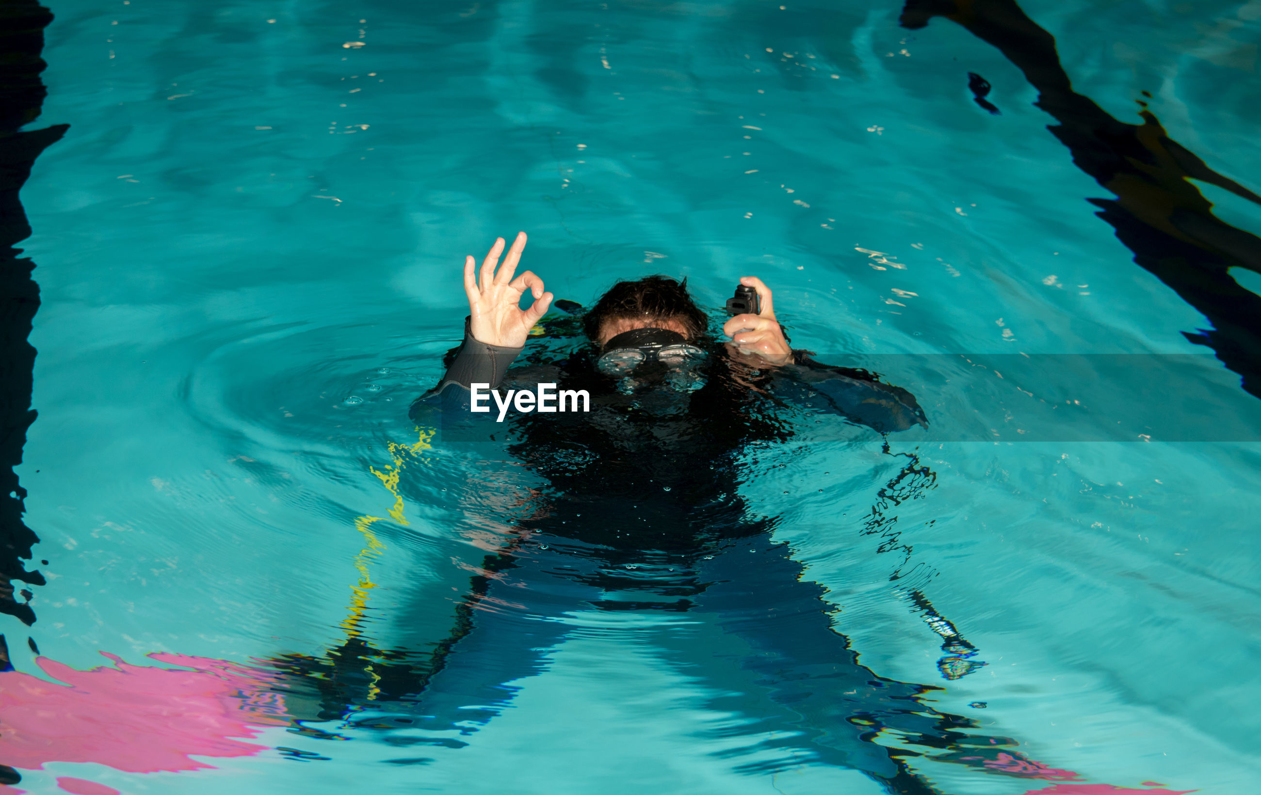 High angle view of young woman gesturing ok sign while swimming in pool