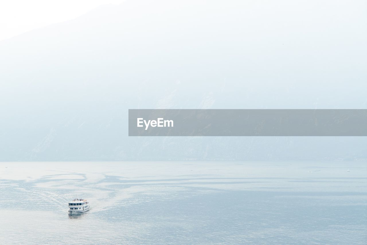 Ferry Boat Sailing In Sea Against Sky During Foggy Weather