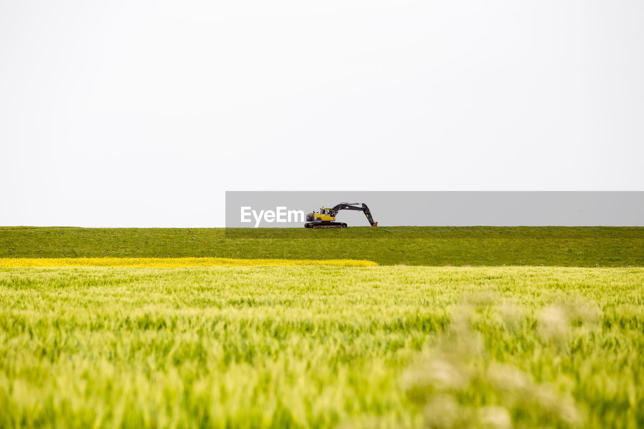 Excavator On Grassy Field Against Clear Sky