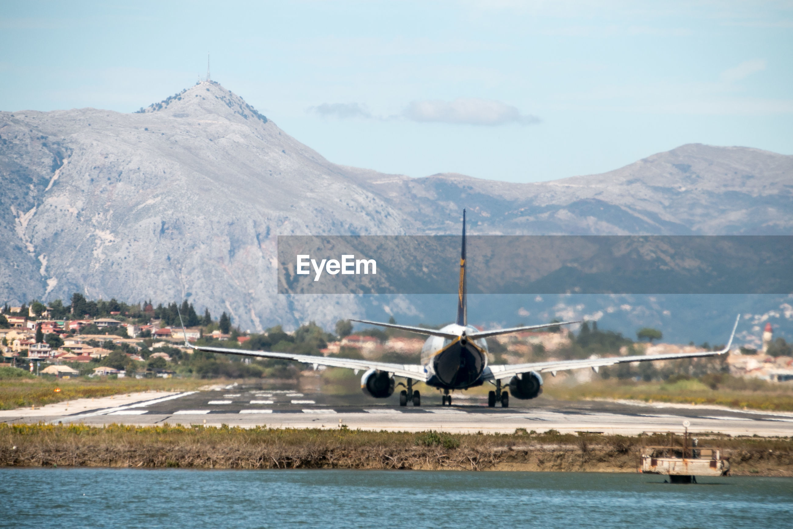 Airplane on sea by mountains against sky