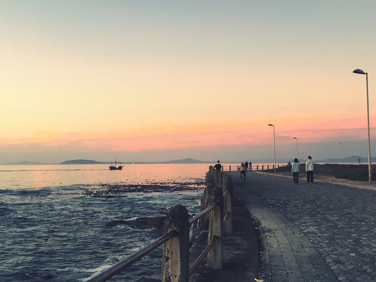sunset, sky, sea, water, orange color, beauty in nature, scenics - nature, nature, street, copy space, street light, beach, group of people, architecture, pier, railing, footpath, real people, incidental people, outdoors, horizon over water, promenade