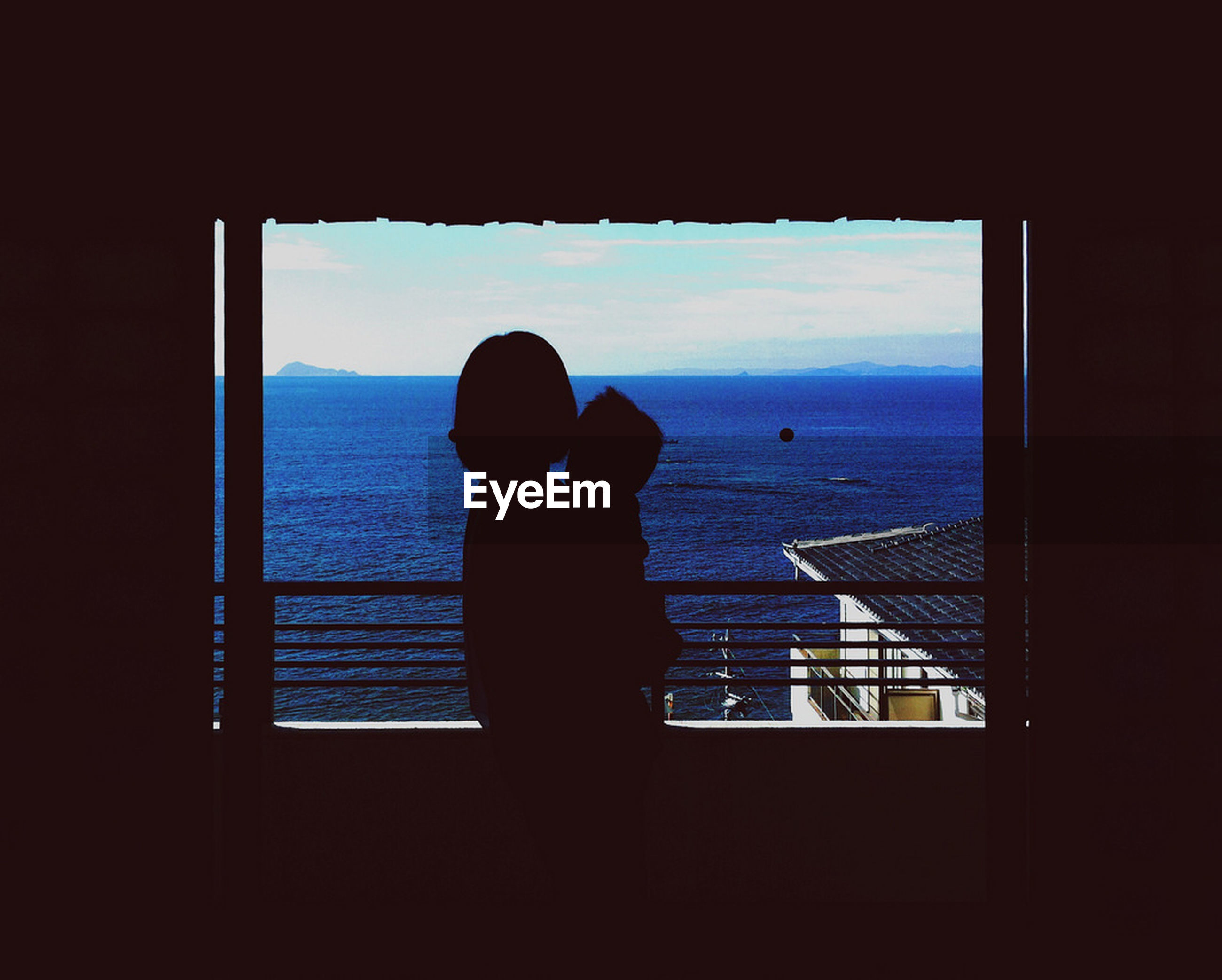 Silhouette couple looking at sea view from window
