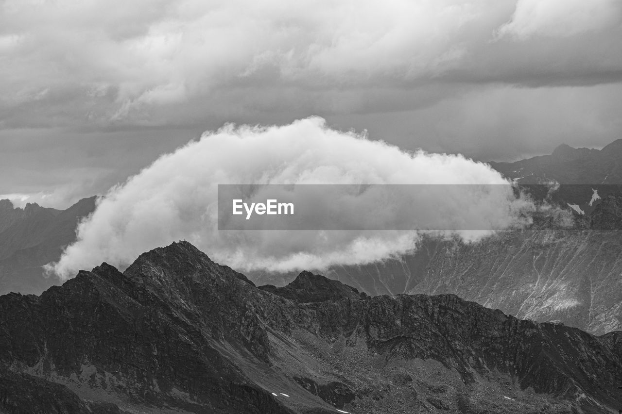 Scenic view of mountains against sky and clouds