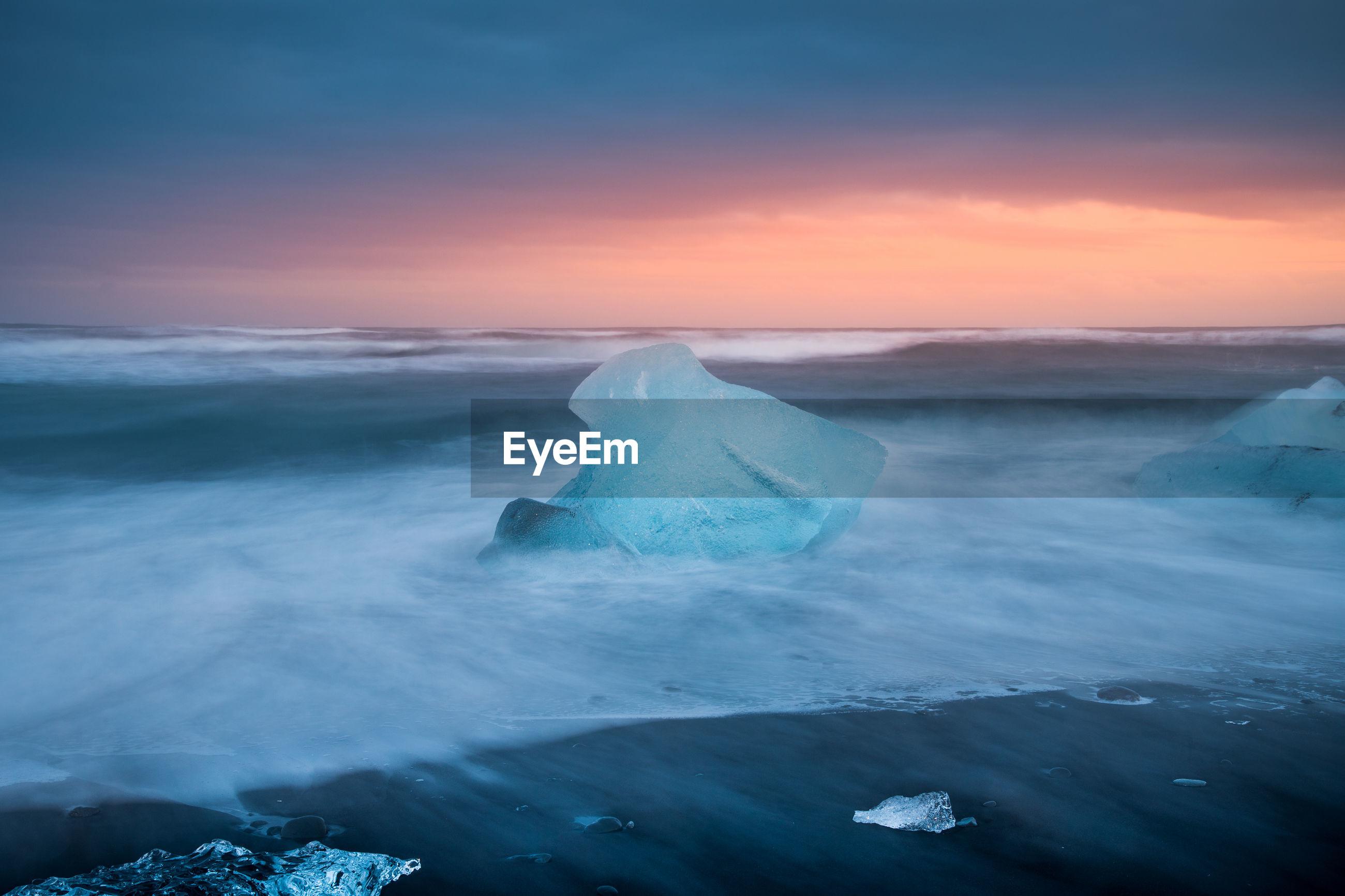 Glacier on shore against cloudy sky
