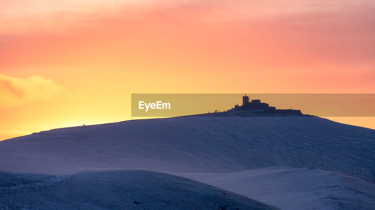 BUILDING ON MOUNTAIN DURING SUNSET