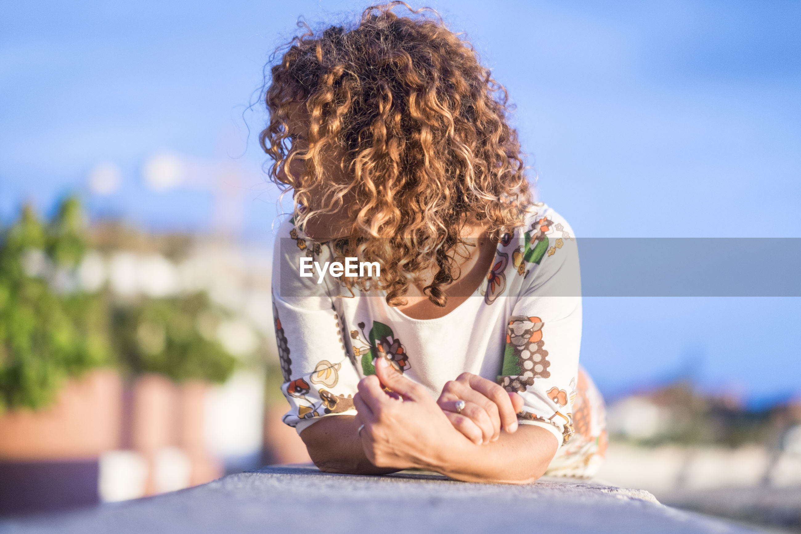 Woman lying on retaining wall against sky
