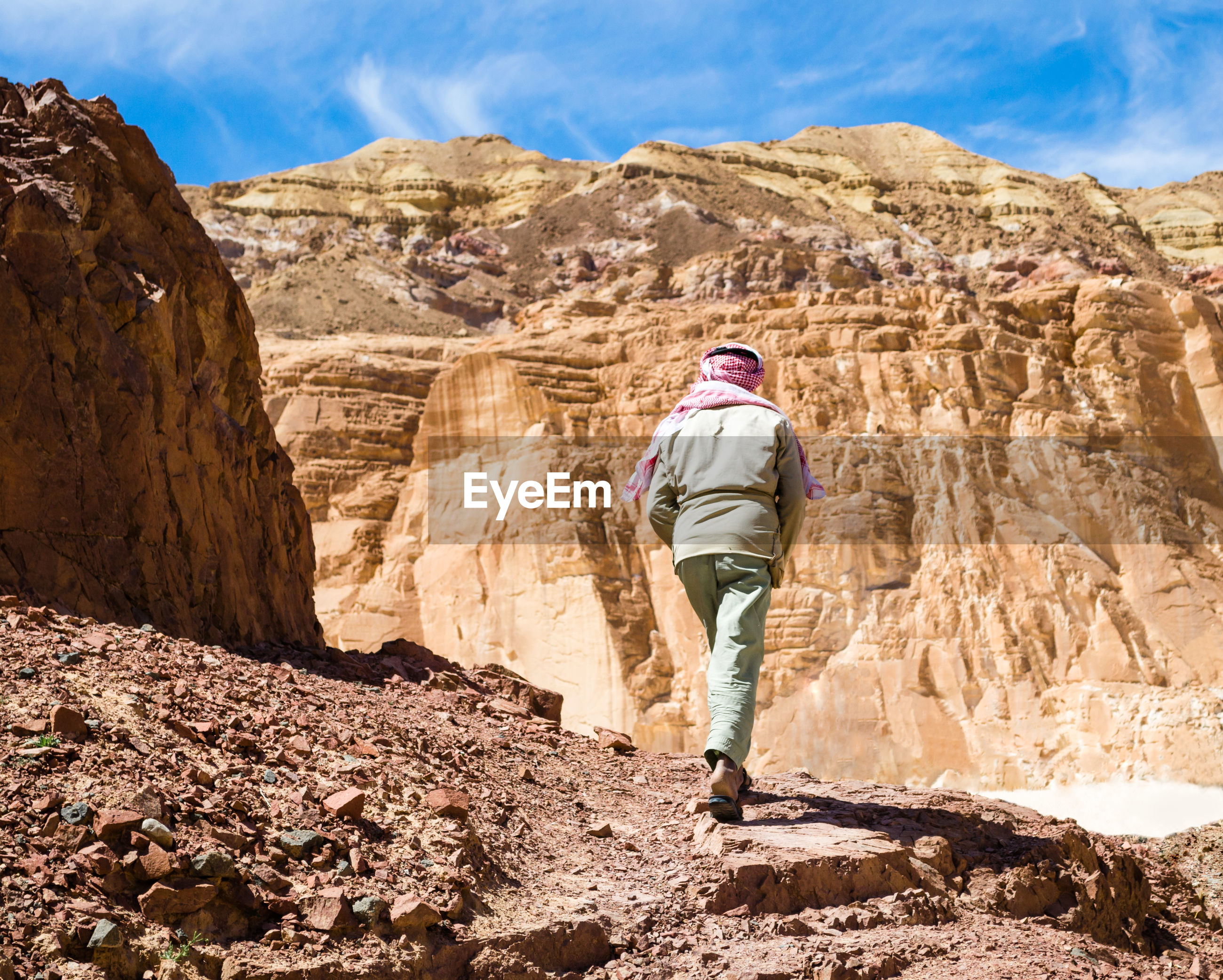 Rear view of man walking on rock formation