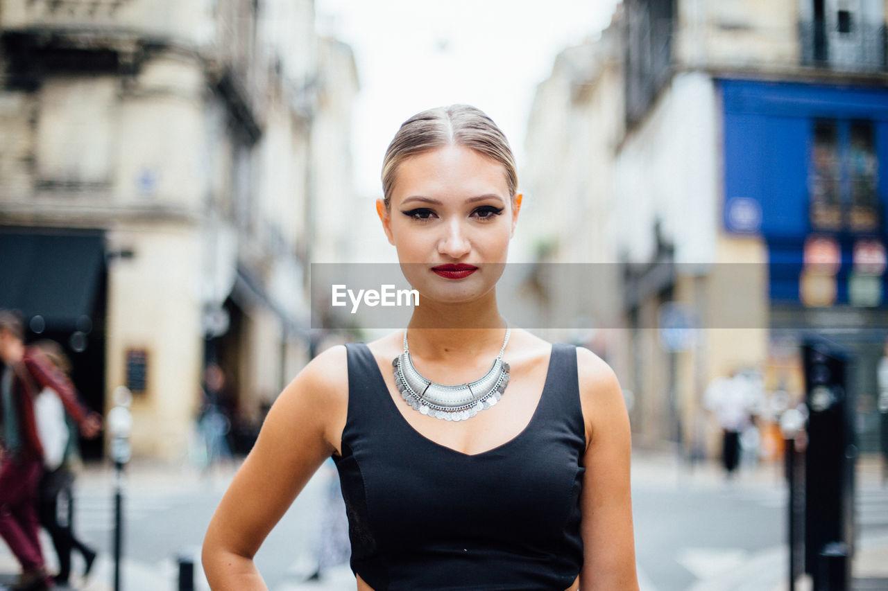 Portrait of beautiful model standing on city street