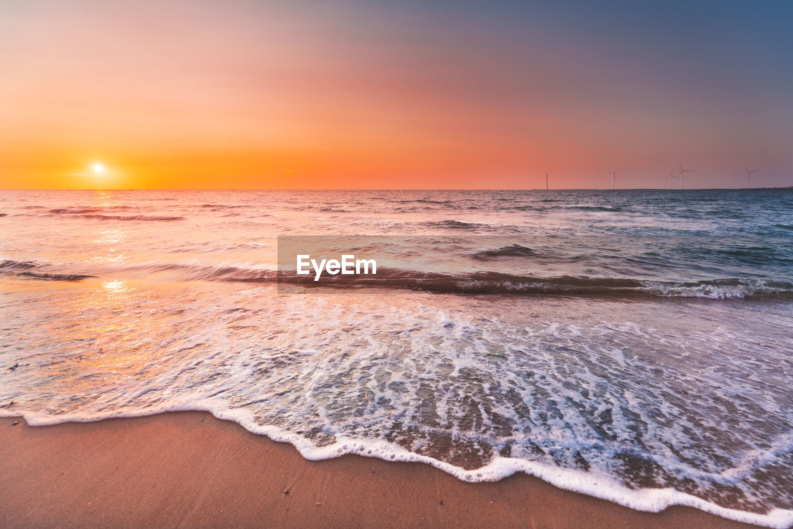 SCENIC VIEW OF BEACH AT SUNSET