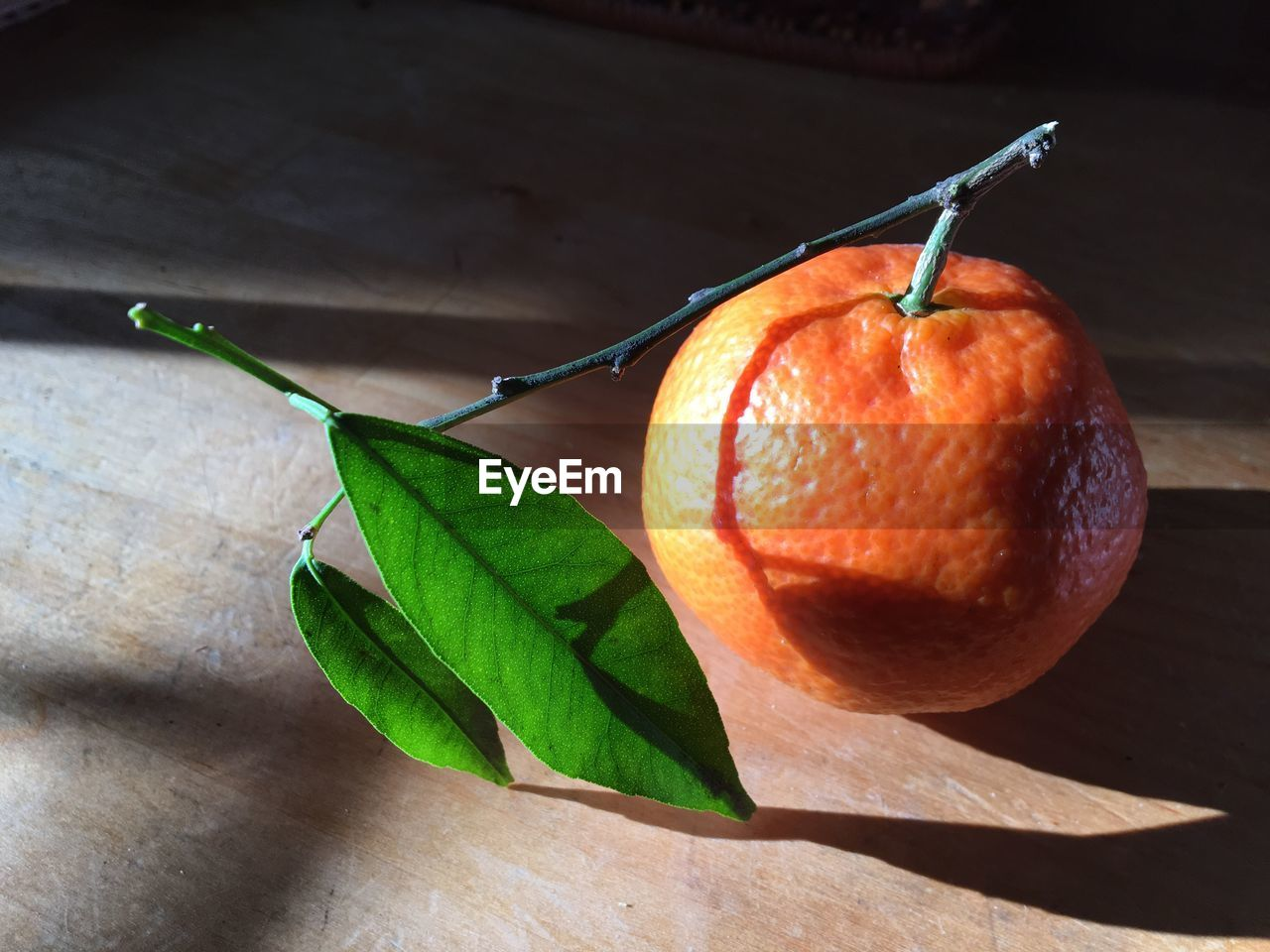 plant part, food, leaf, healthy eating, food and drink, fruit, freshness, close-up, no people, wellbeing, nature, still life, table, green color, orange color, orange, focus on foreground, indoors, plant stem, shadow, ripe