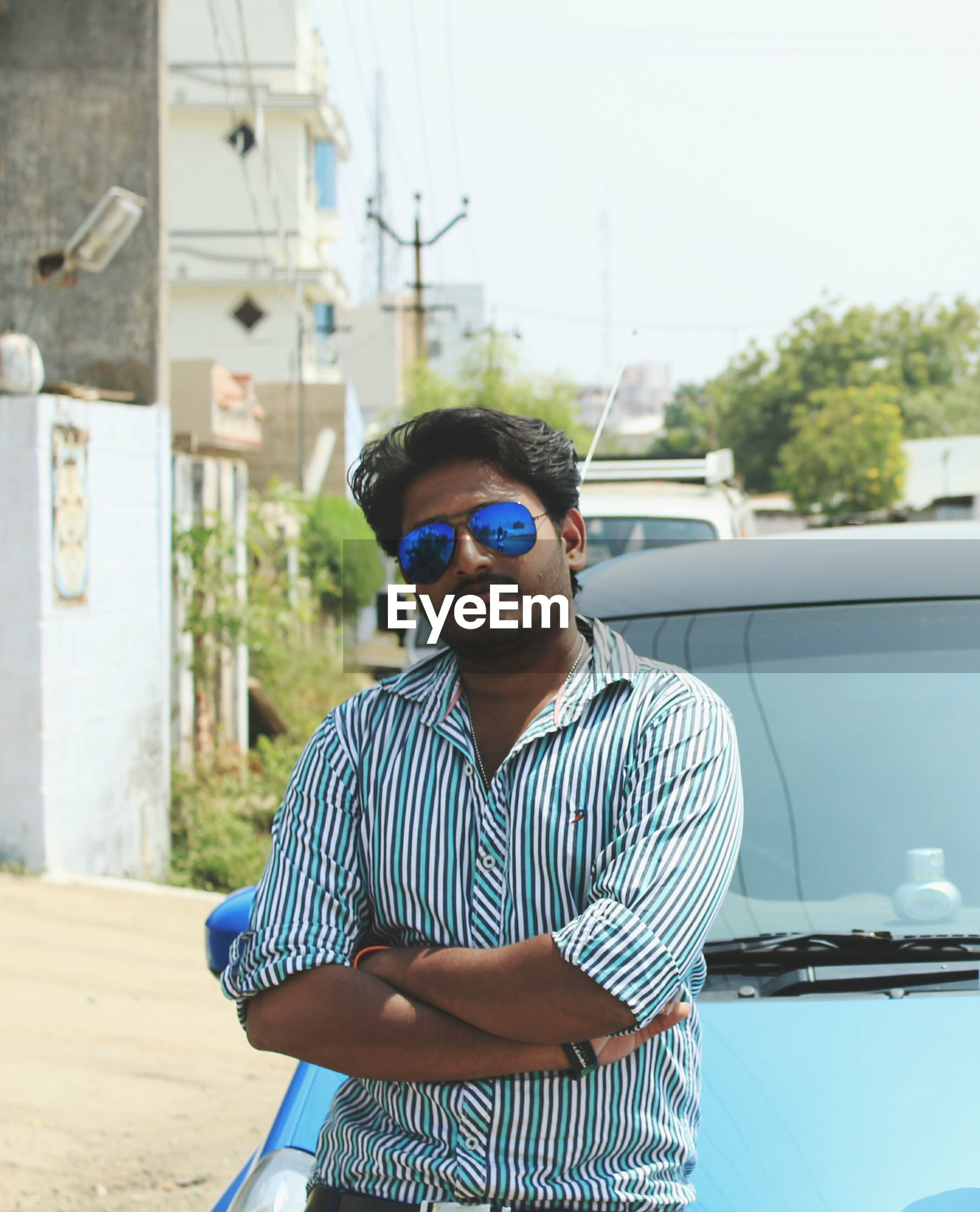young adult, young men, real people, sunglasses, striped, one person, front view, lifestyles, focus on foreground, casual clothing, standing, leisure activity, looking at camera, eyeglasses, day, outdoors, portrait, technology, architecture, young women