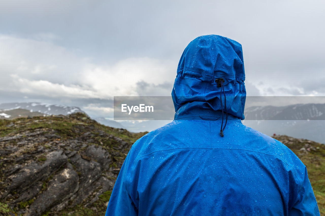 Rear View Of Hiker In Raincoat Standing At Lyngen Alps During Rainy Season