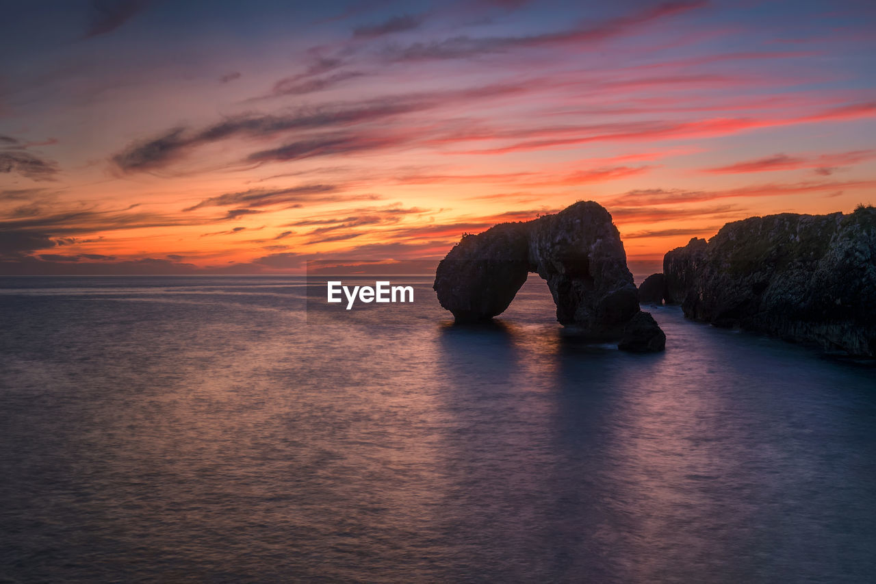 sunset, water, sky, sea, beauty in nature, scenics - nature, tranquility, tranquil scene, cloud - sky, horizon over water, idyllic, waterfront, rock, orange color, horizon, solid, rock - object, no people, nature, stack rock