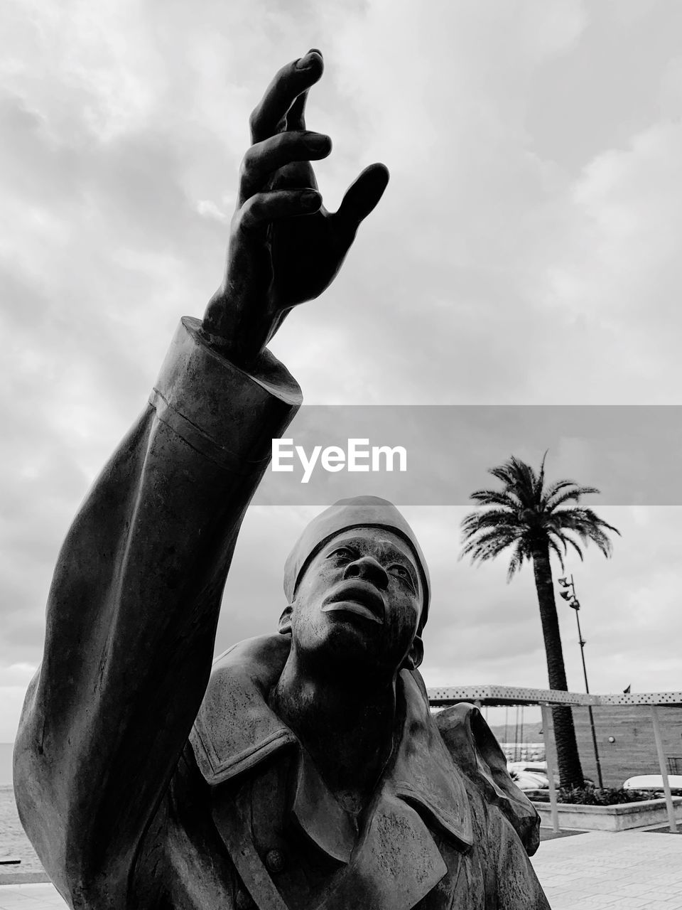 sculpture, statue, art and craft, sky, representation, human representation, low angle view, cloud - sky, male likeness, architecture, palm tree, nature, creativity, craft, day, tropical climate, no people, outdoors, built structure, religion