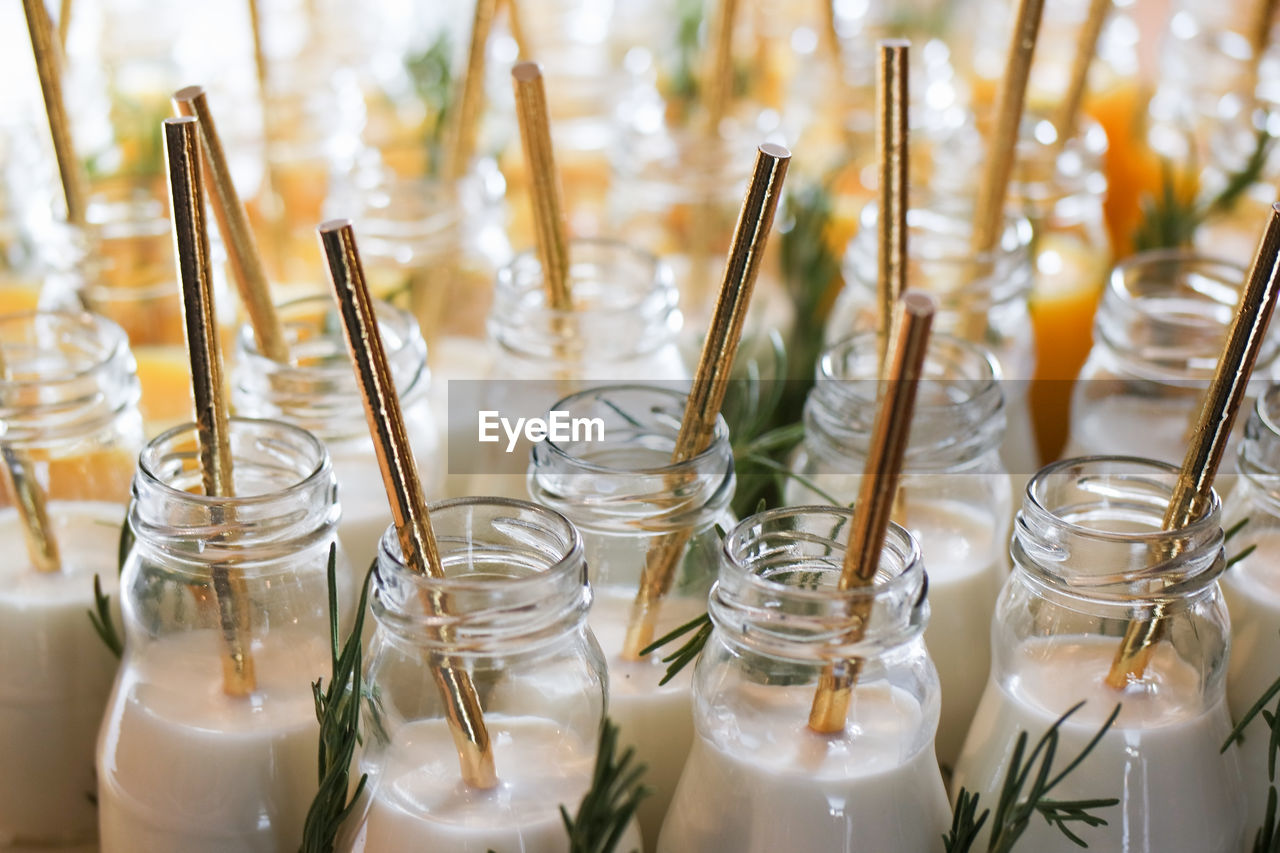 Close-Up Of Jars With Milk And Drinking Straws