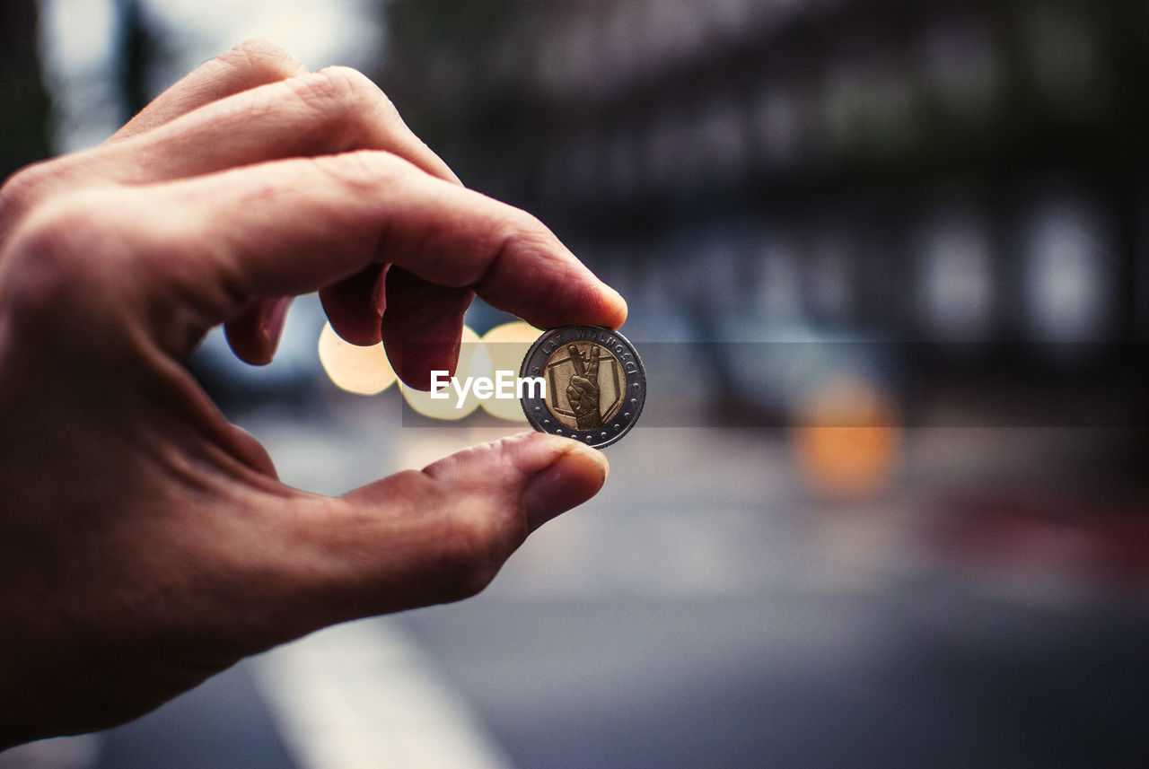 Cropped Image Of Person Holding Coin Between Thumb And Finger