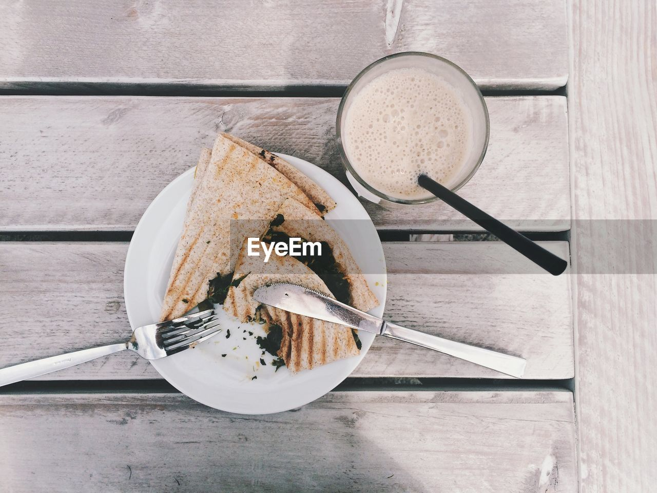 High angle view of quesadilla and milkshake on wooden table