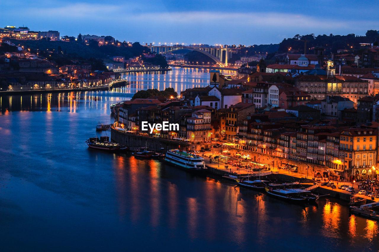 VIEW OF ILLUMINATED CITY AT RIVERBANK