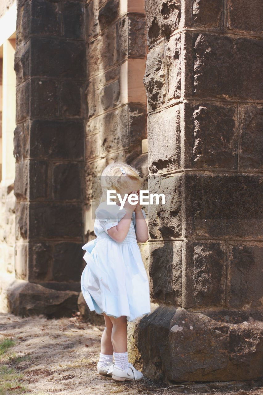 Full length of cute girl covering face while standing by wall