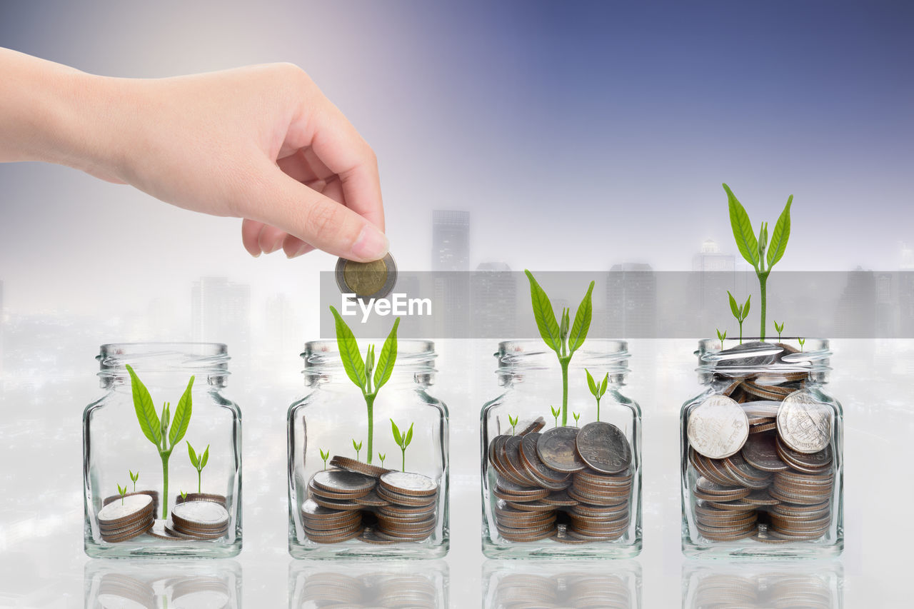 Digital composite image of woman collecting coins in jar with plants