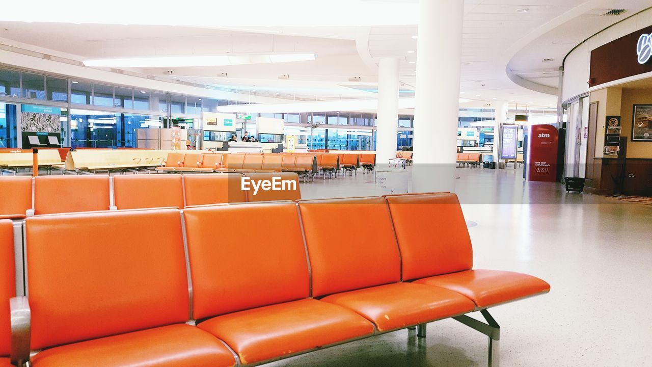 seat, chair, indoors, absence, empty, transportation, orange color, architecture, airport, no people, flooring, waiting room, built structure, architectural column, travel, airport departure area, lobby, in a row, journey, mode of transportation, modern, ceiling, airport terminal, waiting
