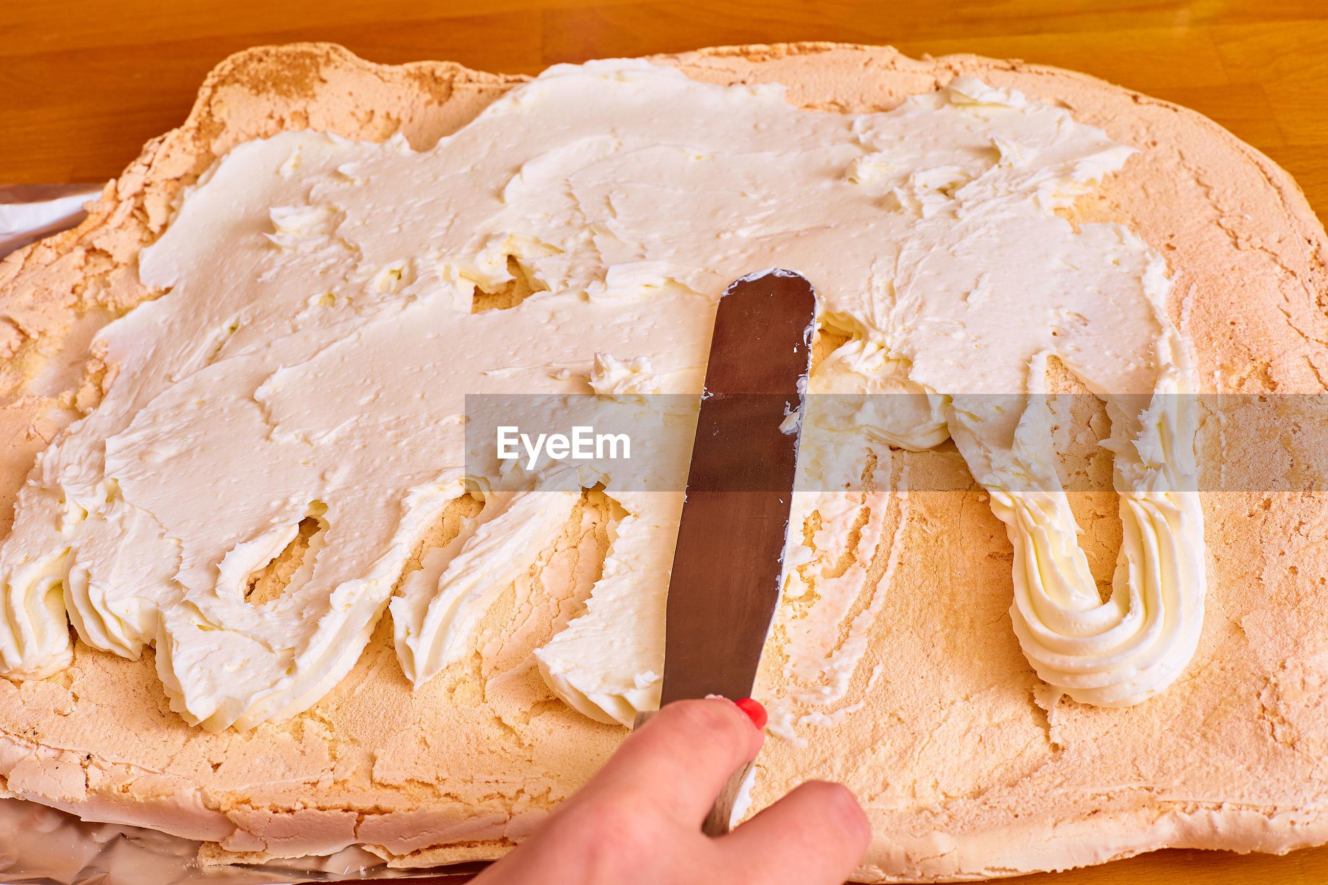 HIGH ANGLE VIEW OF HAND HOLDING CHOCOLATE CAKE