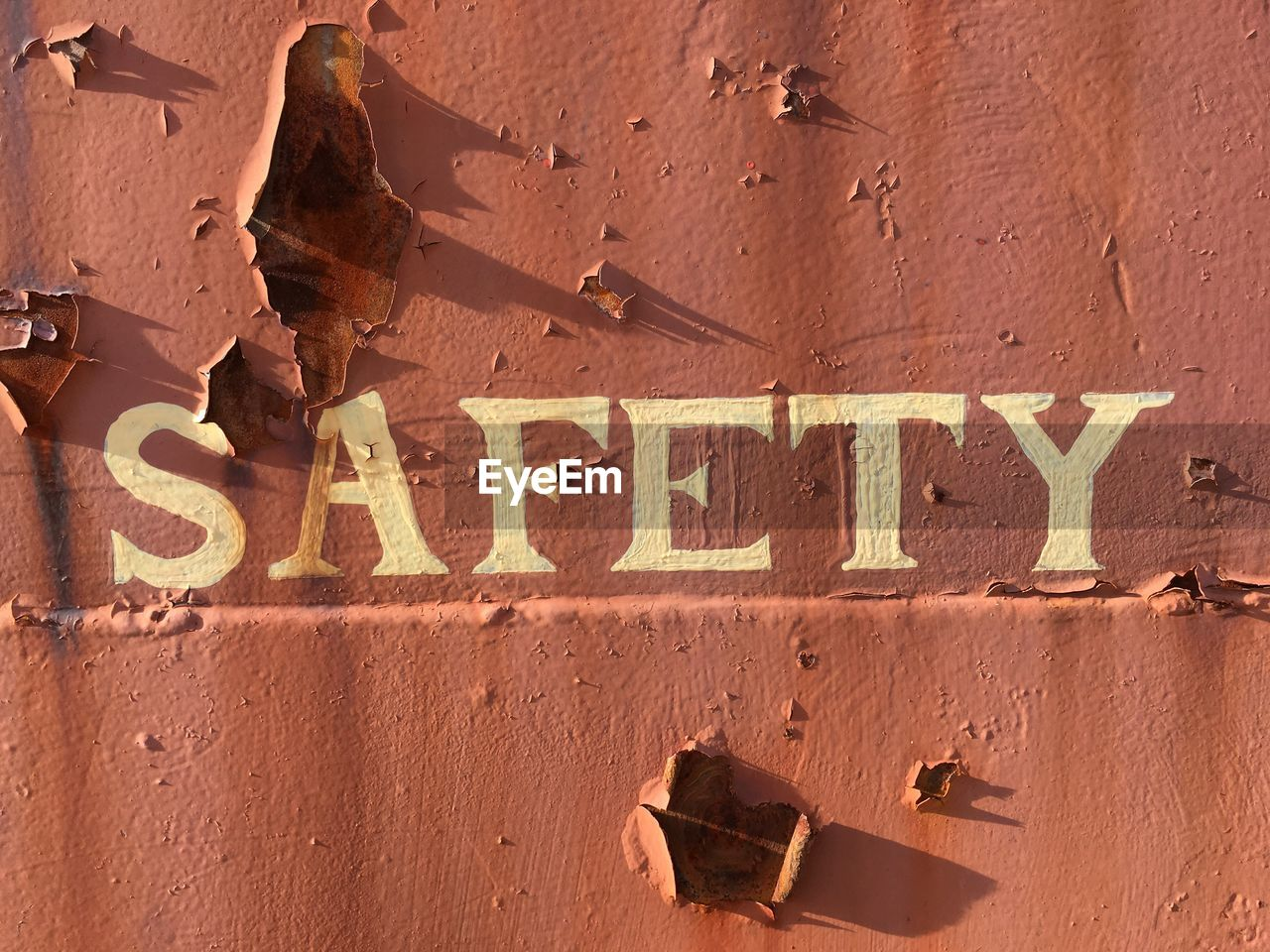 Close-Up Of Safety Text On Rusty Wall