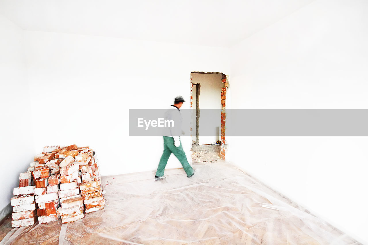 Man Walking By Wall Against Bricks At Home During Renovation