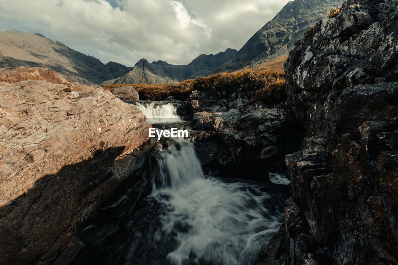 Scenic View Of Waterfall And Mountains Against Cloudy Sky