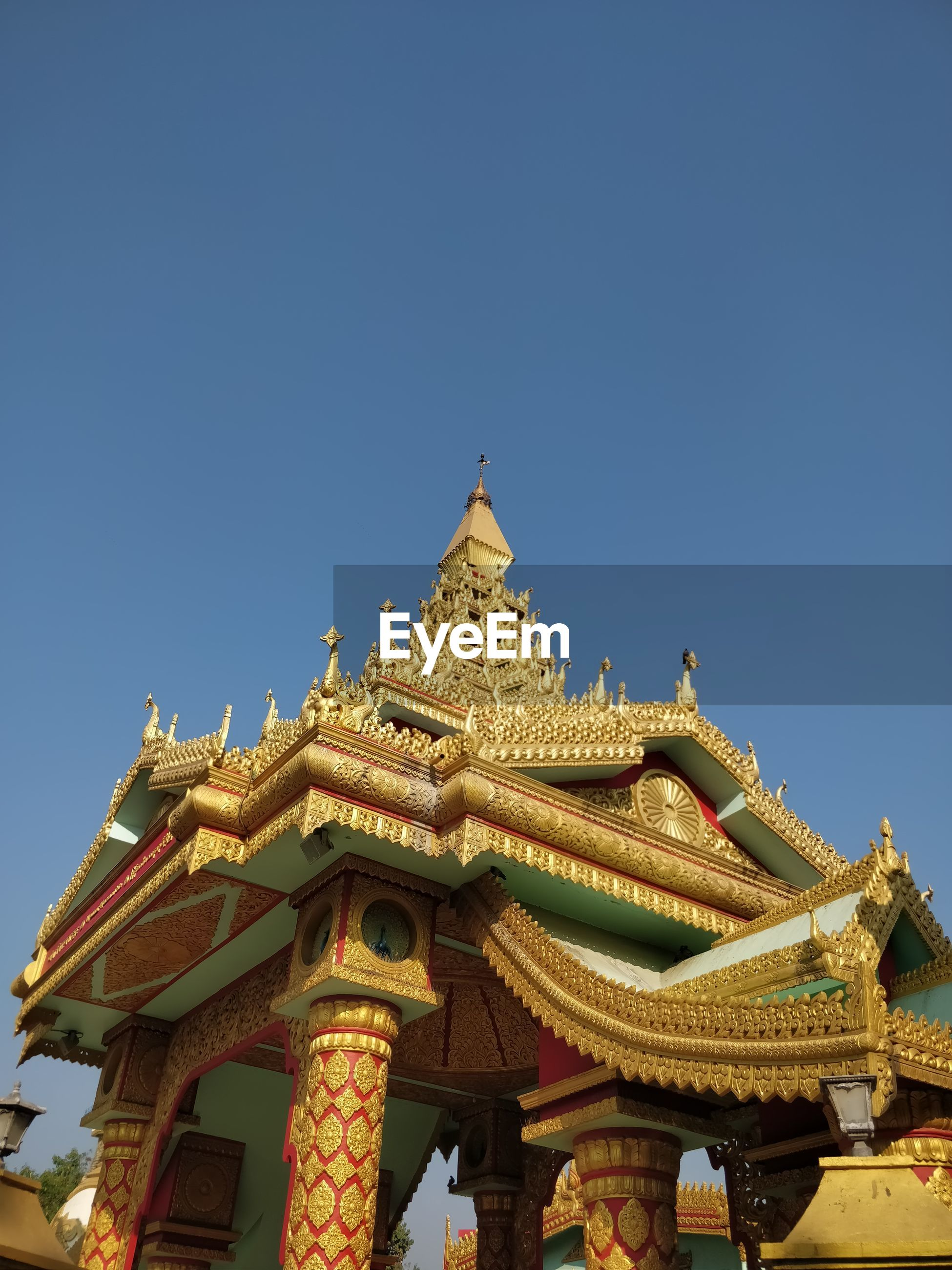 Low angle view of temple and building against clear sky