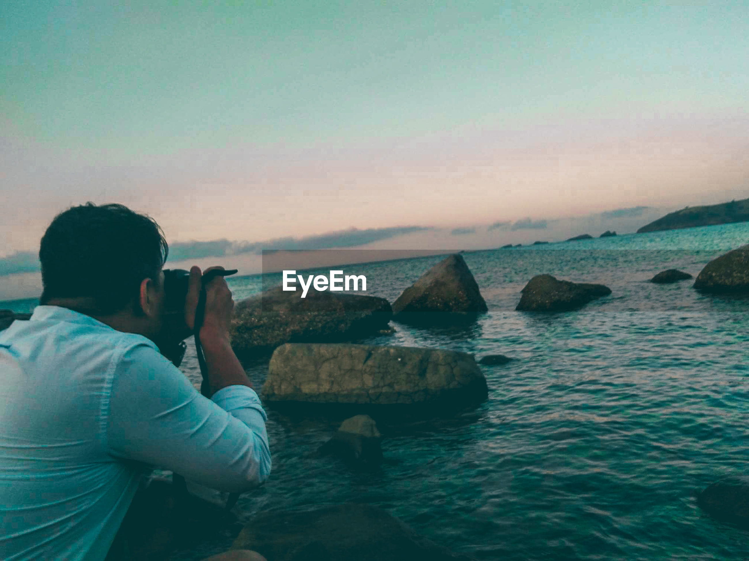 water, sea, photography themes, photographing, technology, sky, real people, activity, scenics - nature, leisure activity, lifestyles, sunset, rock, rock - object, nature, beauty in nature, solid, one person, horizon over water, wireless technology, digital camera, outdoors, photographer