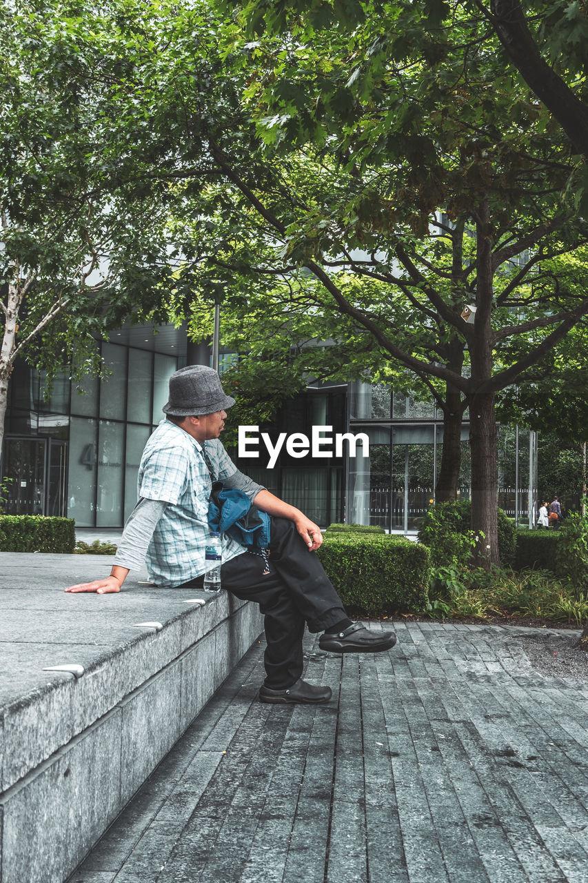 MAN SITTING ON FOOTPATH IN CITY