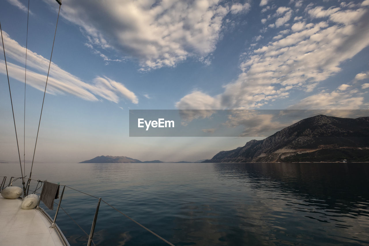 sky, cloud - sky, water, scenics - nature, beauty in nature, sea, mountain, tranquility, nature, tranquil scene, no people, nautical vessel, transportation, non-urban scene, mode of transportation, day, waterfront, outdoors, idyllic, sailboat, yacht