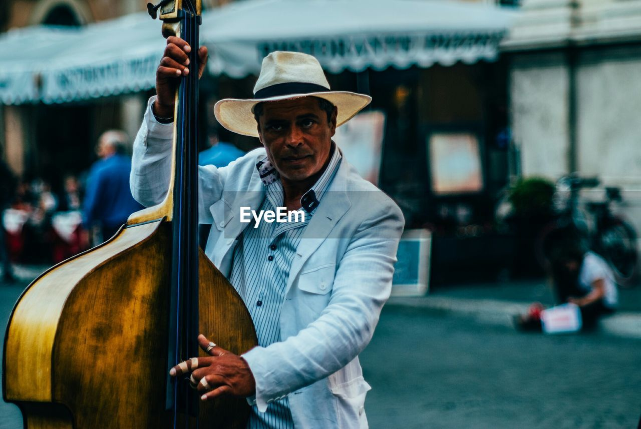 Portrait Of Mid Adult Man Playing String Instrument While Standing On Street