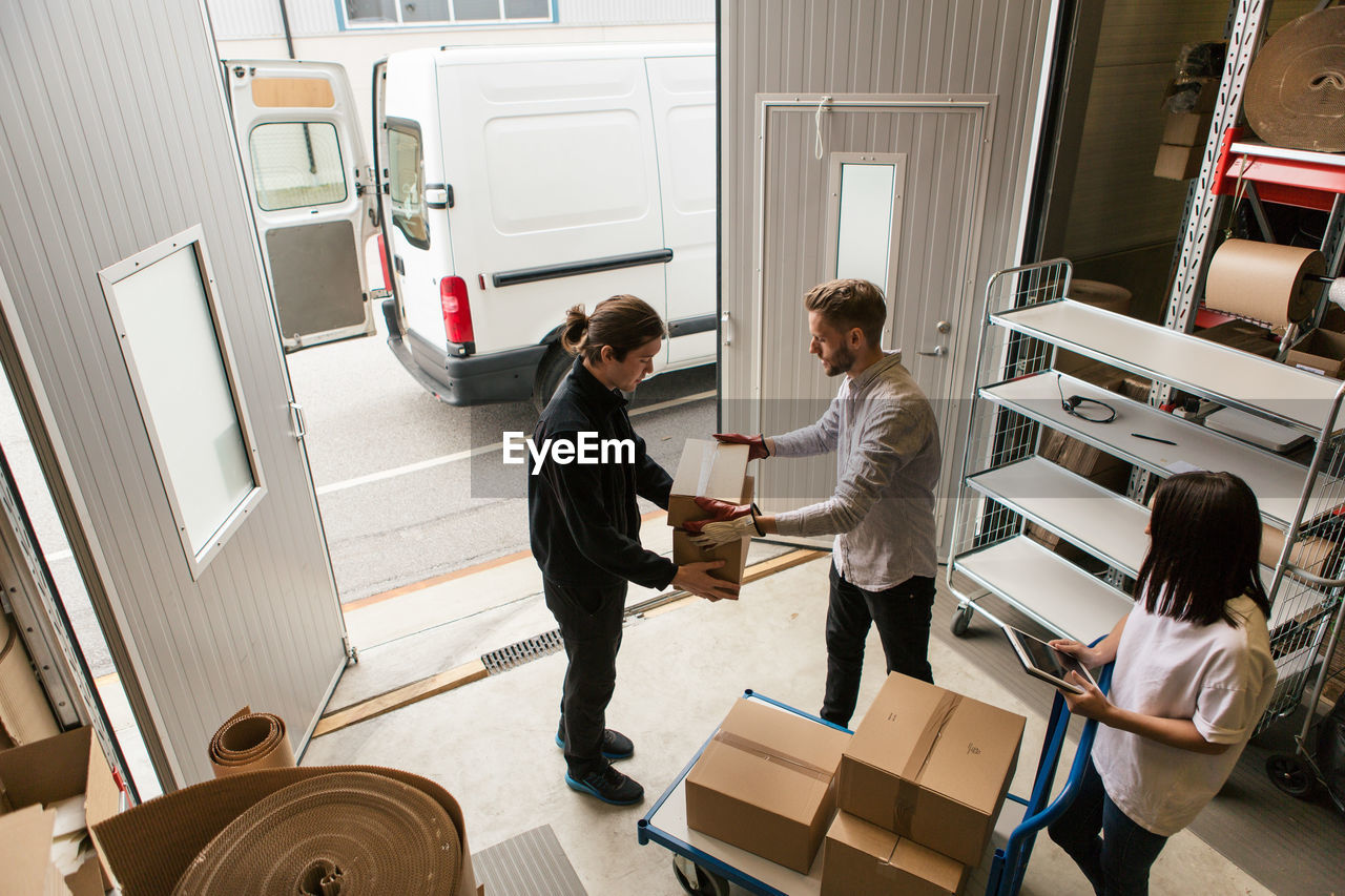 High angle view of male coworkers delivering boxes while female is using digital tablet