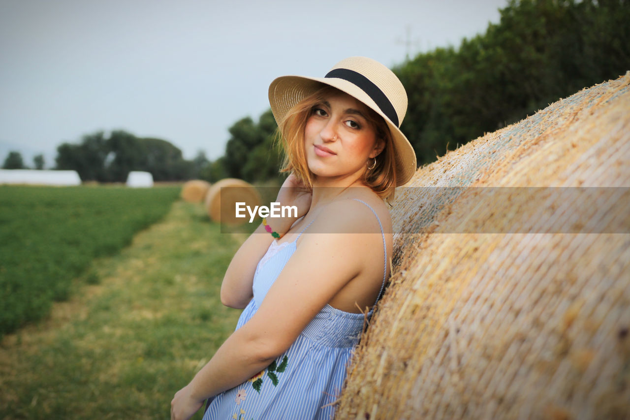 Portrait of young woman standing by haystack