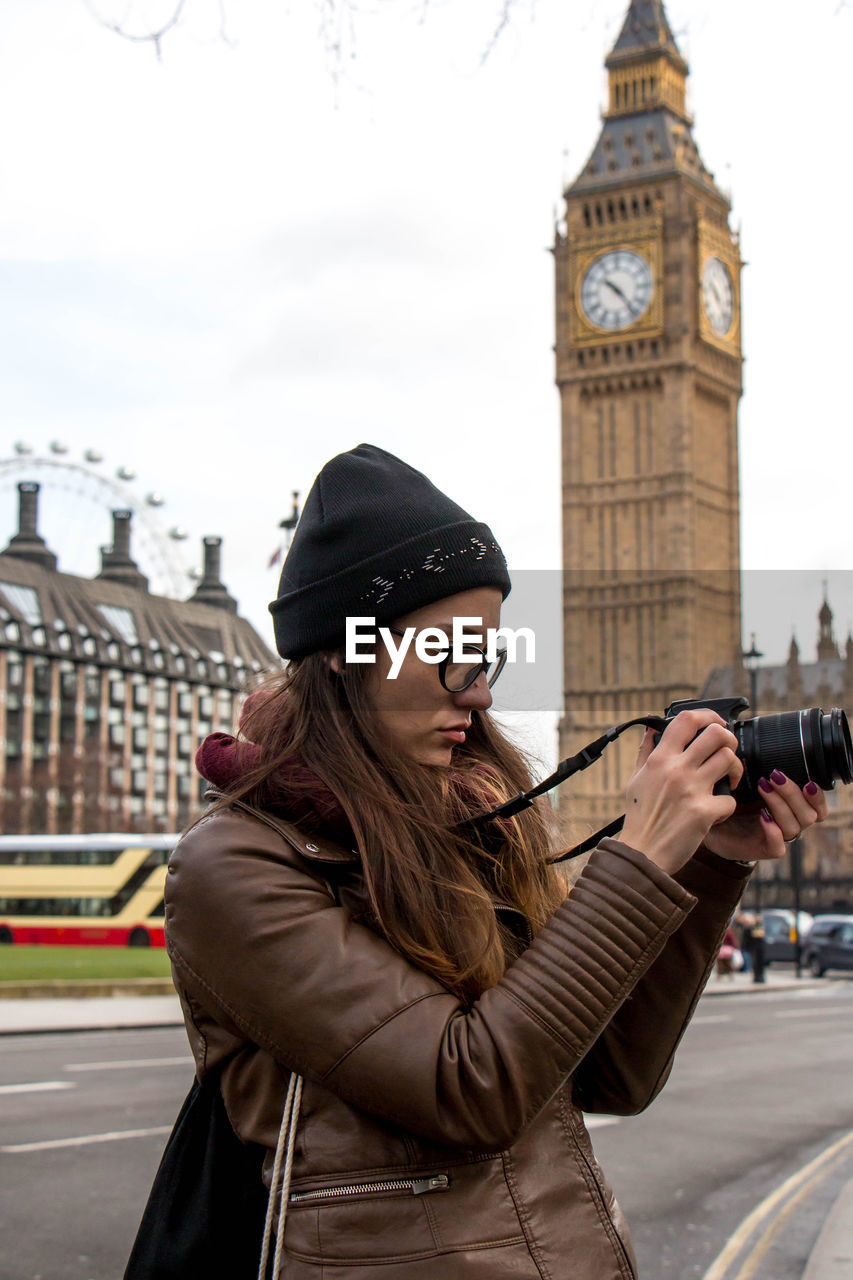 Woman photographing while standing against big ben
