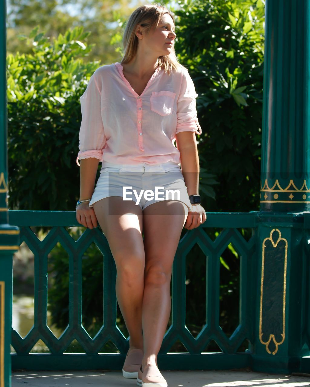 FULL LENGTH OF YOUNG WOMAN LOOKING AT SWIMMING POOL