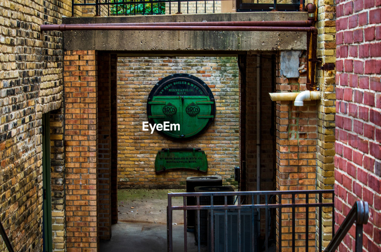 brick, brick wall, wall, wall - building feature, no people, day, architecture, built structure, building exterior, metal, outdoors, green color, old, technology, communication, close-up, window, machinery, building, focus on foreground