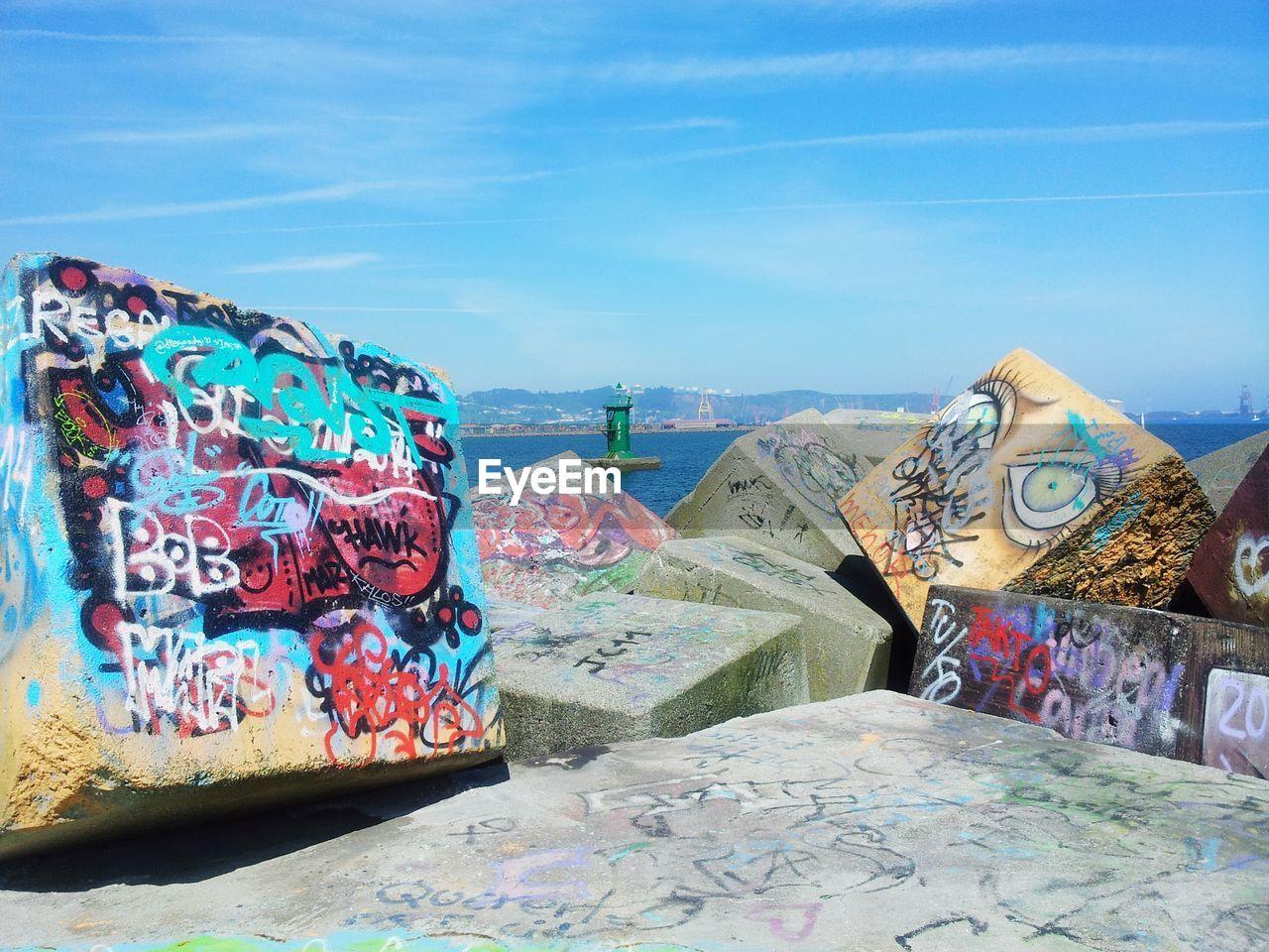 Graffiti on groyne rocks against blue sky