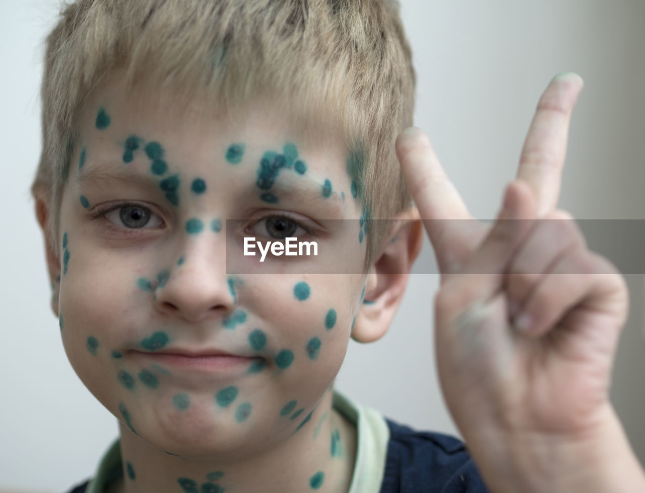 Close-up portrait of cute boy with face paint gesturing peace sign at home