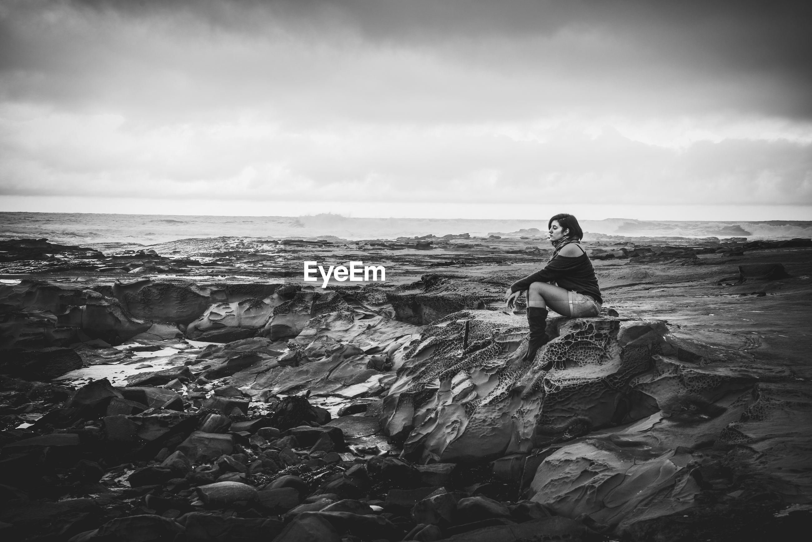 Side view of woman sitting on rock at beach against cloudy sky