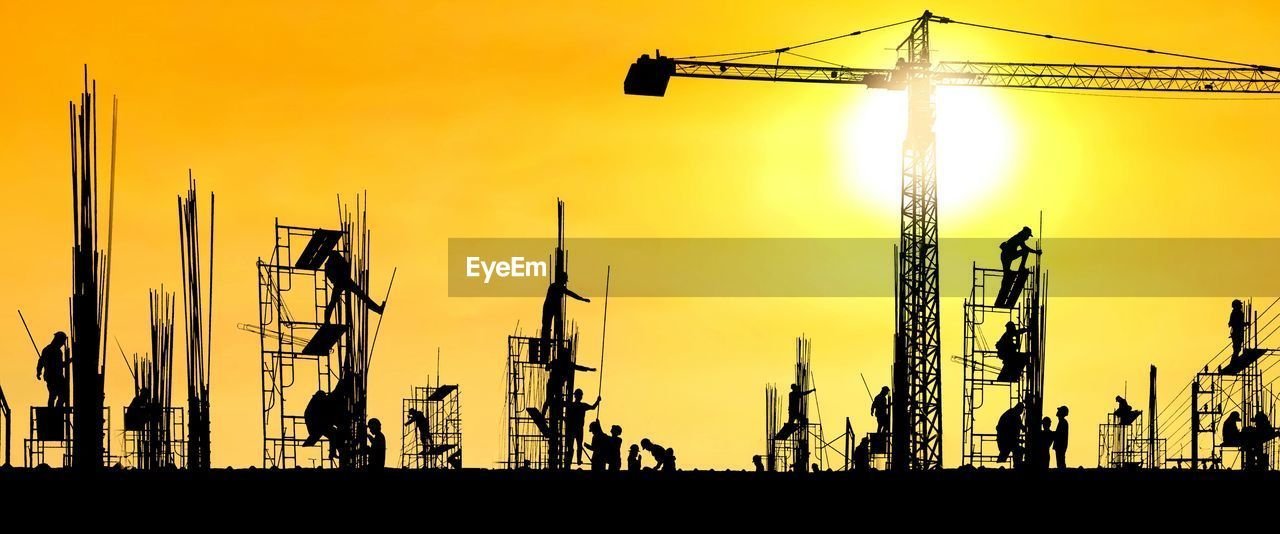 sky, sunset, silhouette, crane - construction machinery, orange color, construction industry, development, machinery, nature, construction site, industry, architecture, sun, sunlight, construction equipment, group of people, built structure, crane, outdoors, transportation