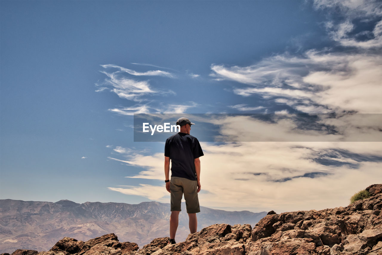 Rear view of senior man standing on cliff against cloudy sky