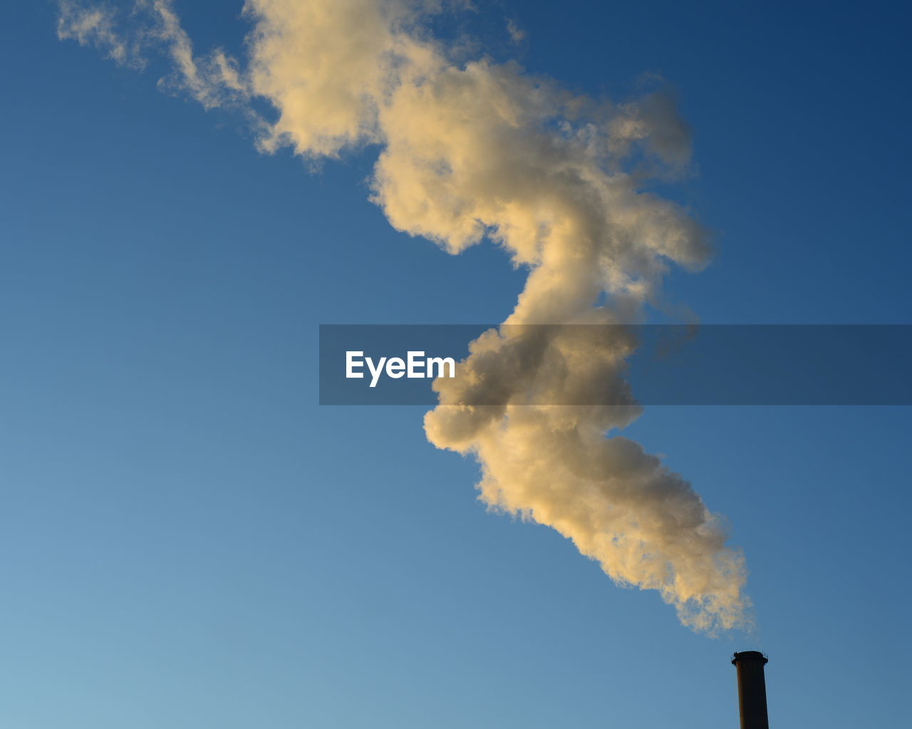 Low Angle View Of Smoke Emitting From Chimney Against Blue Sky