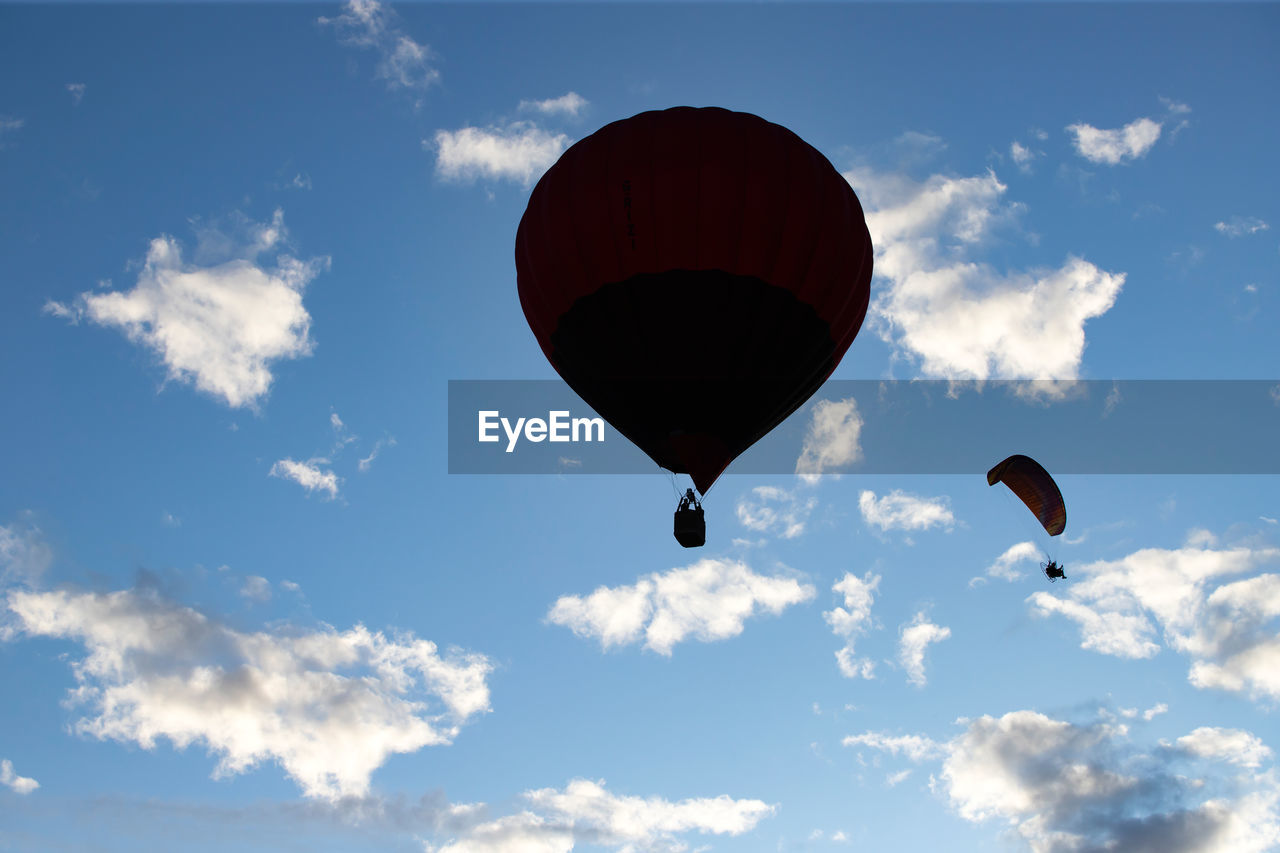 cloud - sky, sky, mid-air, low angle view, flying, parachute, adventure, freedom, transportation, extreme sports, nature, balloon, air vehicle, hot air balloon, day, red, sport, paragliding, exhilaration, unrecognizable person, outdoors, parasailing