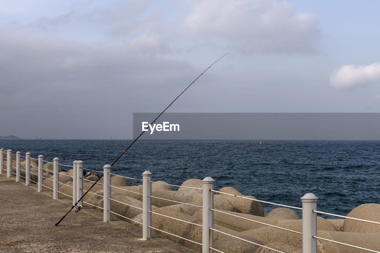 sea, horizon over water, sky, horizon, water, beauty in nature, tranquil scene, scenics - nature, cloud - sky, tranquility, day, railing, nature, non-urban scene, rod, no people, fishing rod, beach, land, outdoors