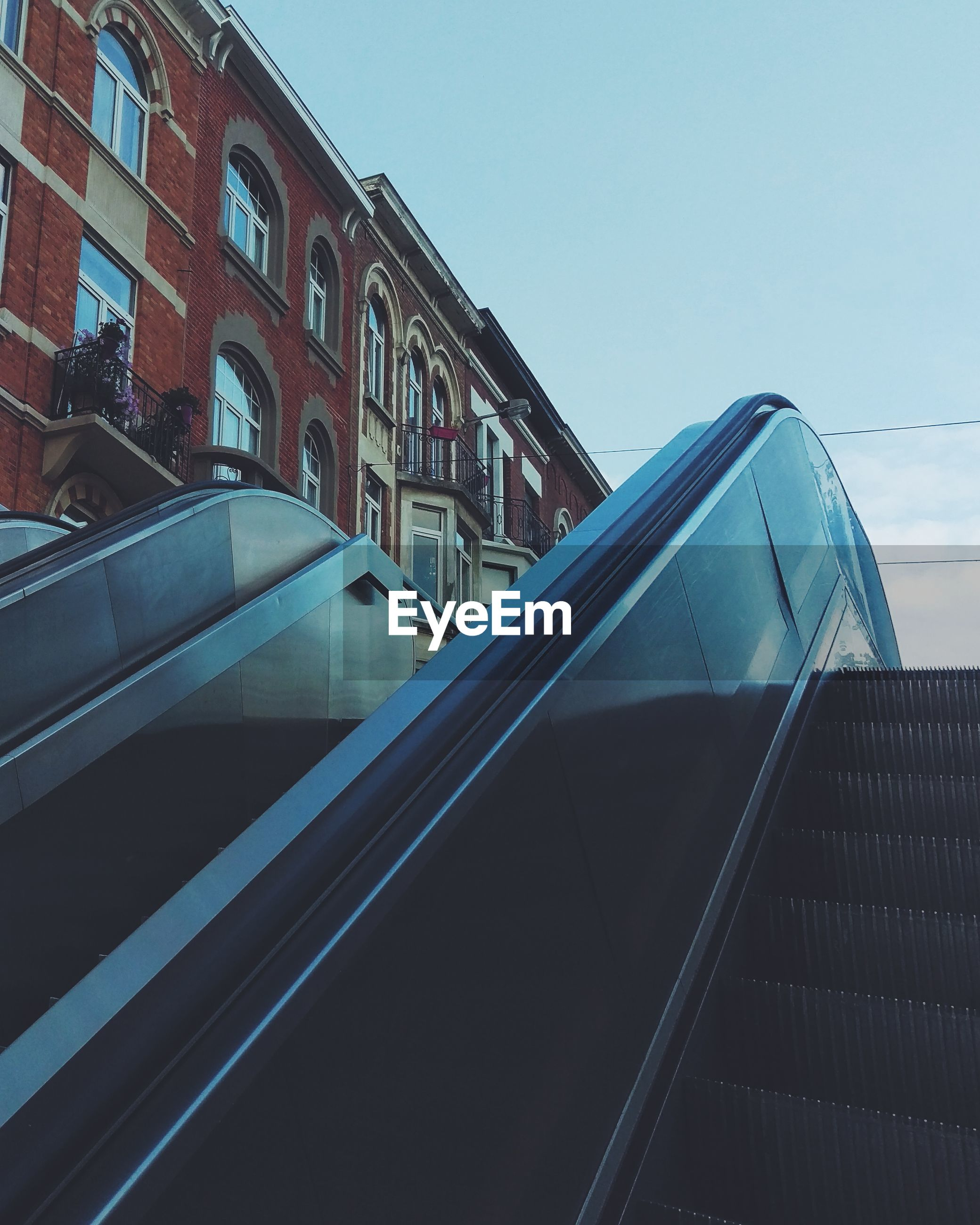 Low angle view of escalator by building against sky