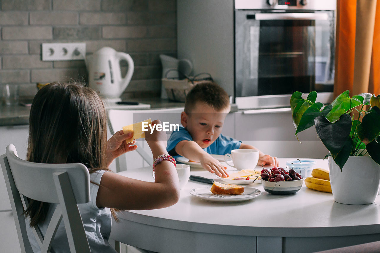 Sister and brother with food on table at home